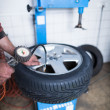Auto mechanic in a garage checking the air pressure in a tyre wi - Stock Photo