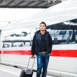 Just arrived: handsome young man walking along a platform at a modern train station - Stockfoto