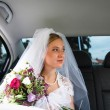Portrait of a beautiful young bride waiting in the car on her wa — Stock Photo
