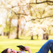 Young woman using her tablet computer while relaxing outdoors in a park on a lovely spring day — Stock Photo