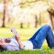 Young woman using her tablet computer while relaxing outdoors in a park on a lovely spring day — Stock Photo #17128867