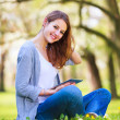 Young woman using her tablet computer while relaxing outdoors in — Stock Photo