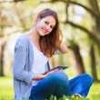 Young woman using her tablet computer while relaxing outdoors in — Stock Photo #17128879