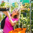 Young woman buying flowers at a garden center — Stock Photo #17128899