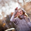 Autumn portrait: young woman dressed in a warm woolen cardigan posing outside in a city park — Stock Photo #17129021