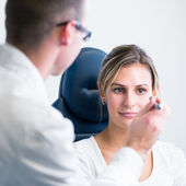 Optometry concept - handsome young man having her eyes examined — ストック写真