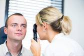Optometry concept - handsome young man having her eyes examined — Stock Photo