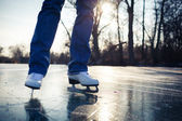 Young woman ice skating outdoors on a pond on a beautiful sunny day — Stok fotoğraf