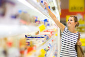 Krásná mladá žena nakupování na mléčné výrobky v supermarketu s potravinami — Stock fotografie