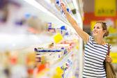 Schöne junge frau, die für milchprodukte in einem lebensmittelgeschäft-supermarkt einkaufen — Stockfoto