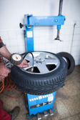 Auto mechanic in a garage checking the air pressure in a tyre wi — Stok fotoğraf