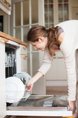 Housework: young woman putting dishes in the dishwasher — Stock Photo