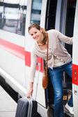 Pretty young woman boarding a train — Stock Photo