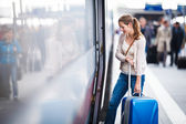 Pretty young woman at a train station — Stockfoto
