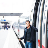 Train travel - Handsome young man taking a train — Stock Photo