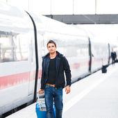 только что прибыл: красивый молодой человек, прогулки вдоль платформы на современной железнодорожной станции — Стоковое фото