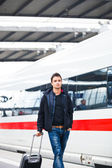 Just arrived: handsome young man walking along a platform at a modern train station — Stock Photo