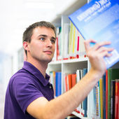 Handsome college student in library — Stock Photo