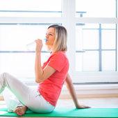 Bella giovane donna rinfrescante durante l'allenamento a casa — Foto Stock