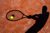 Shadow of a tennis player in action on a tennis court (conceptua — Stok fotoğraf