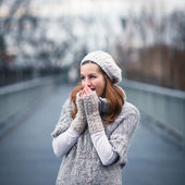 Autumn portrait: young woman dressed in a warm woolen cardigan posing outside in a city park — Stok fotoğraf