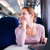 Young woman traveling by train, watching the passing country side while standing in the train corridor — Stock Photo