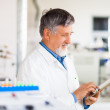 Senior scientist using his tablet computer at work — Stock Photo #18534947