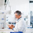 Senior scientist using his tablet computer at work — Stock Photo #18534959