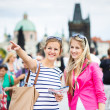 Two female tourists walking along the Charles Bridge — Stock Photo #18535057