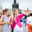 Two female tourists walking along the Charles Bridge — Stock Photo #18535059