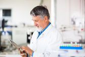 Senior scientist using his tablet computer at work — Stock Photo