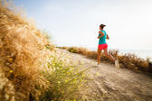 Young woman on her evening jog along the seacoast — Stock Photo