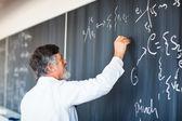 Profesor de química senior escribiendo en la pizarra — Foto de Stock