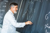 Senior chemistry professor writing on the board — Stock Photo