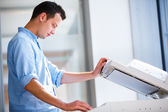 Handsome young man using a copy machine — Stock Photo