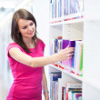 Pretty young college student in a library — Stock Photo #18577169