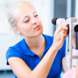 Optometry concept - pretty, young female patient having her eyes examined — Stock Photo