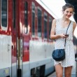 Pretty young woman at a train station - Stok fotoğraf