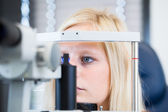 Optometry concept - pretty, young female patient having her eyes examined — Stok fotoğraf