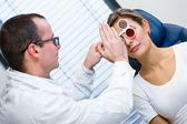 Optometri kavramı - genç ve güzel kadın gözleri muayene olması — Stok fotoğraf