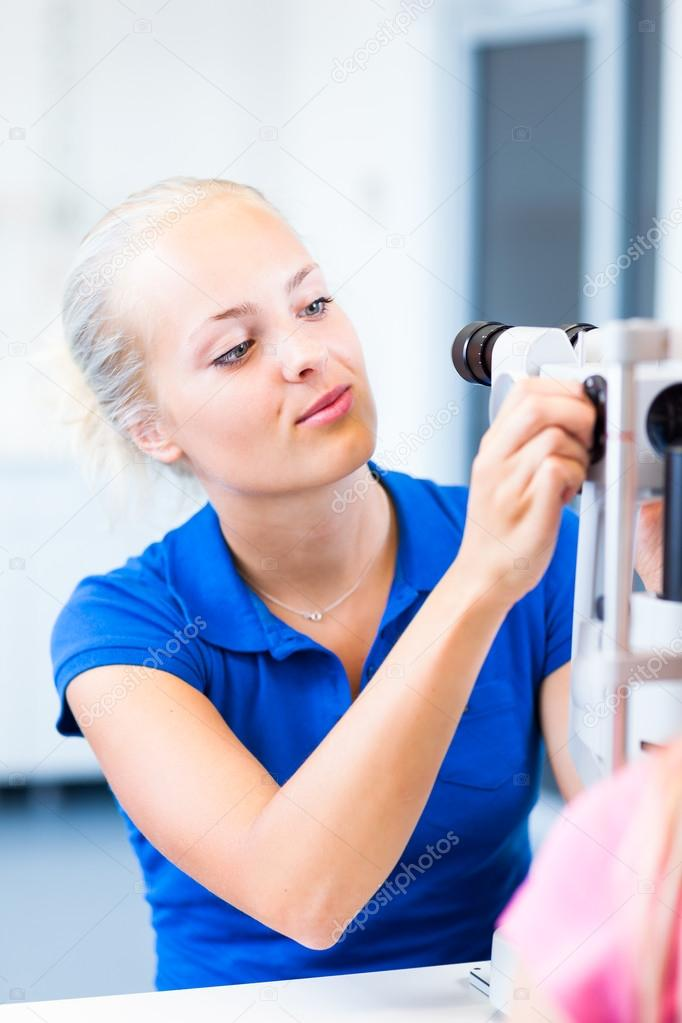 Optometry concept - pretty, young female patient having her eyes examined by an eye doctor — Stock Photo #18577217