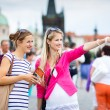 Two female tourists walking along the Charles Bridge while sightseeing in Prague — Stock Photo #19598445