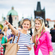 Two female tourists walking along the Charles Bridge while sightseeing in Prague — Stock Photo