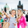 Two female tourists walking along the Charles Bridge while sightseeing in Prague — Stock Photo #19598447