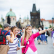 Two female tourists walking along the Charles Bridge while sightseeing in Prague — Stock Photo #19598449
