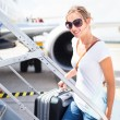 Departure - young woman at an airport about to board an aircraft - Stock Photo