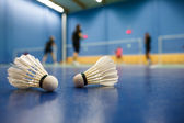 Badminton - badminton courts with players competing, shuttlecocks in the foreground — Stok fotoğraf
