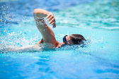 Meu jovem, o rastreamento da frente a nadar em uma piscina — Foto Stock