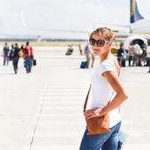 Vertrek - jonge vrouw op een luchthaven ongeveer aan boord van een vliegtuig — Stockfoto