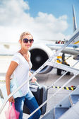 Departure - young woman at an airport about to board an aircraft — Stockfoto